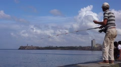 A fisherman stands on the Malecon waterfront in Havana, Cuba. Stock Footage