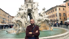 Young man relaxing by the Fountain of the Four Rivers in Rome, Italy, slow motio Stock Footage