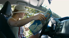 Girl reading map for directions in the car during Road Trip Stock Footage