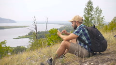 Tourist man He is sitting in the mountains, and talking on the phone . men wi Stock Footage