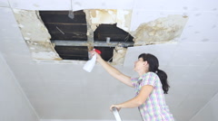 Young Woman cleaning mold on ceiling.Ceiling panels damaged huge hole in roof Stock Footage