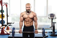 Bodybuilder in the gym training with bar Stock Photos