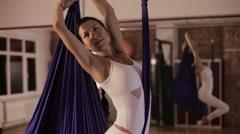 Anti-gravity Yoga, woman doing yoga exercises indoor Stock Footage