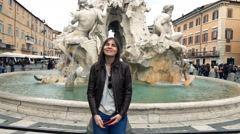 Happy woman relaxing by the Fountain of the Four Rivers in Rome, Italy, slow mot Stock Footage