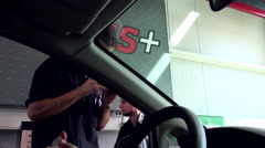 Car mechanic giving new oil change mile tape for customer at Canadian tire store Stock Footage