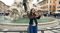 Woman taking selfie photo by Fountain of the Four Rivers in Rome, Italy, slow mo Stock Footage