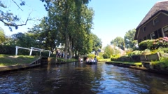 Boat ride in the main canal of the famous village of Giethoorn on a summer day. Stock Footage
