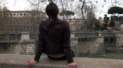 Young woman relaxing while sitting on ledge by river in city  Stock Footage
