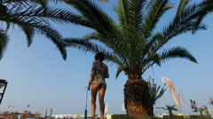 Rear view of Attractive girl walking on beach under palm trees, low angle Stock Footage