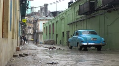 People walk on the old city of Havana, Cuba in the rain with classic old car Stock Footage