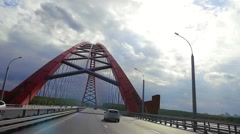 Road through the bridge with cloudy sky and moving cars in slowmotion. 1920x1080 Stock Footage