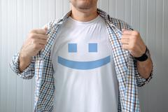 Man stretching shirt to reveal smiley emoticon Stock Photos