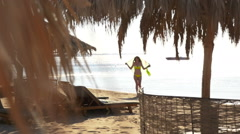Beautiful young woman with pareo goes on the sand at the beach. HD Stock Footage