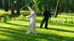 Exercise with a wooden stick. Man and woman practicing qigong. Slow motion. HD Stock Footage