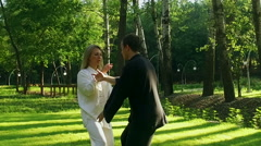 Training in a park. Workout. Woman and man practicing qigong. Slow motion. HD Stock Footage
