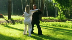 Training in a park. Workout. Woman and man practicing of qigong. Slow motion. HD Stock Footage