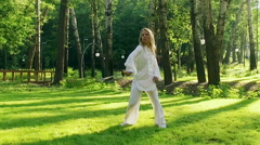 A young woman practicing qigong rotating steel sword around body. Slow motion HD Stock Footage