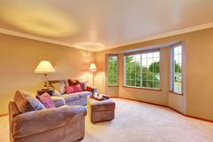 Lovely sitting room with mocha sofas and ottoman. Also carpet floor, beige wa Stock Photos