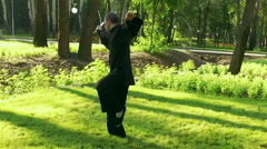 An adult man practicing qigong rotating steel sword around body. Slow motion. HD Stock Footage
