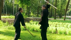 Qigong. Exercise with a wooden stick. Two men practicing qigong. Slow motion. HD Stock Footage