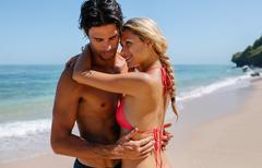 Love couple enjoying honeymoon on tropical beach Stock Photos