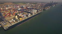Loading and unloading cargo ships in busy port. Aerial view Stock Footage