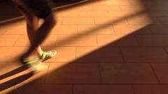 Multiple feet walking on brown sunlit floor. 4K shot Arkistovideo
