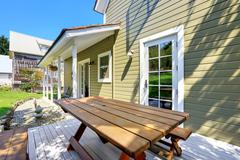 Green olive exterior paint of clapboard siding house. Outdoor patio set and c Stock Photos