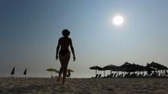 Fashion fit model silhouette walk on empty beach, 4k trekking shot Stock Footage