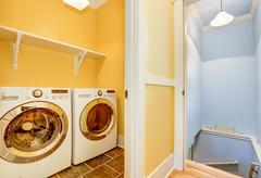 White Modern appliances in small yellow laundry room with open door. Staircas Stock Photos