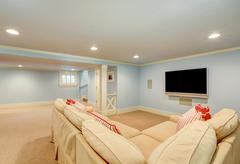 Spacious basement living room interior in pastel blue tones. Beige carpet flo Stock Photos