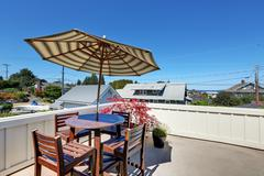 Craftsman house roof top terrace with living area. Table set with umbrella. P Stock Photos