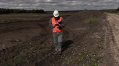 Engineer take pictures in  peat bog Stock Footage