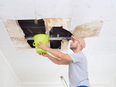 Man Collecting Water In Bucket From Ceiling. Ceiling panels damaged huge hole Stock Photos