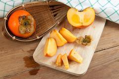 Persimmon yellow color fruits Stock Photos