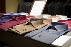 Men's shirts on shelves at a retail store Stock Photos