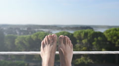 Barefoot male relaxing on seaside vacation at the balcony Stock Footage