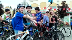 Selfie cyclists, women in helmets sitting on bicycles, make selfie photo mobile Stock Footage