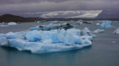 Floating of blue icebergs in Jokulsarlon glacial lagoon in the white nights. Stock Footage