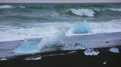 Blocks of ice washed by the waves on Jokursarlon beach Stock Footage