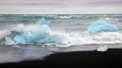 Blocks of ice washed by the waves on Jokursarlon beach. White nights in Icela Stock Footage
