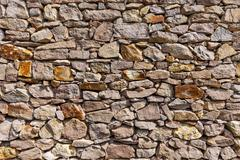 Uneven cracked real stone wall Stock Photos