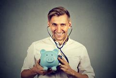 Happy successful man listening to piggy bank with stethoscope Stock Photos