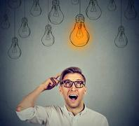 Man in glasses looking up at light bulb has solution Stock Photos