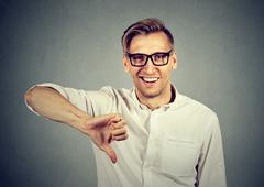 Sarcastic man showing thumbs down sign happy someone lost failed Stock Photos