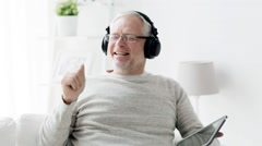 Senior man with tablet pc and headphones at home 91 Stock Footage