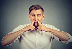 Man pinches nose looks with disgust something stinks bad smell Stock Photos