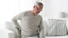 Unhappy senior man suffering from backache at home 103 Stock Footage
