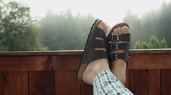 Male feet relaxing on mountain vacation at the balcony Stock Footage