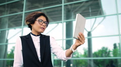 Young beautiful businesswoman talking on tablet, business centre background Stock Footage